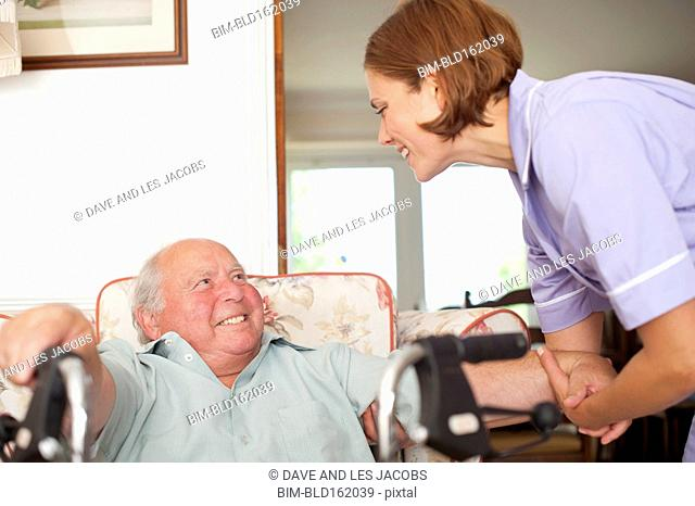 Caucasian nurse talking to patient in home