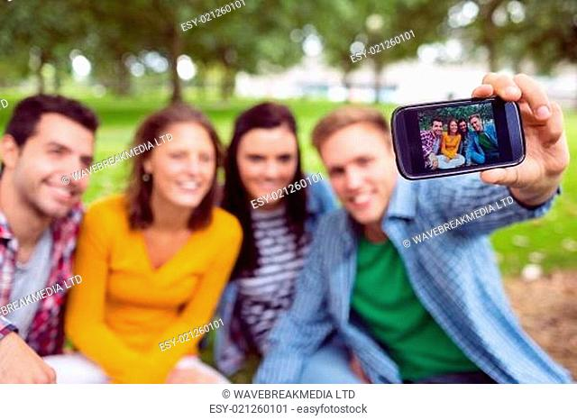 Male taking picture with college friends in park