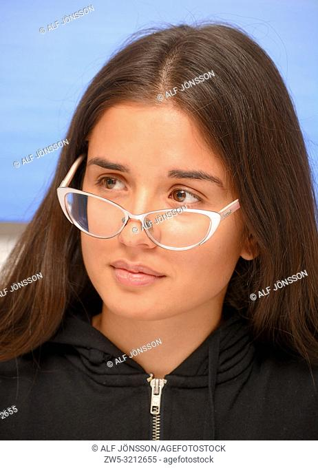 Young dark-haired woman, 30 years old, looking aside over her eye glasses, in Ystad, Sweden