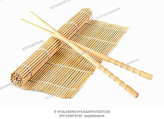 Sushi mat partially deployed and chopsticks isolated on a white background