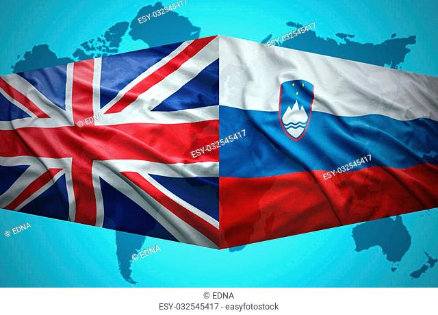 Waving Slovenian and British flags of the political map of the world
