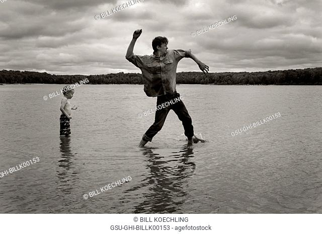 Man Skipping Stones in Lake with Young Boy Standing Behind