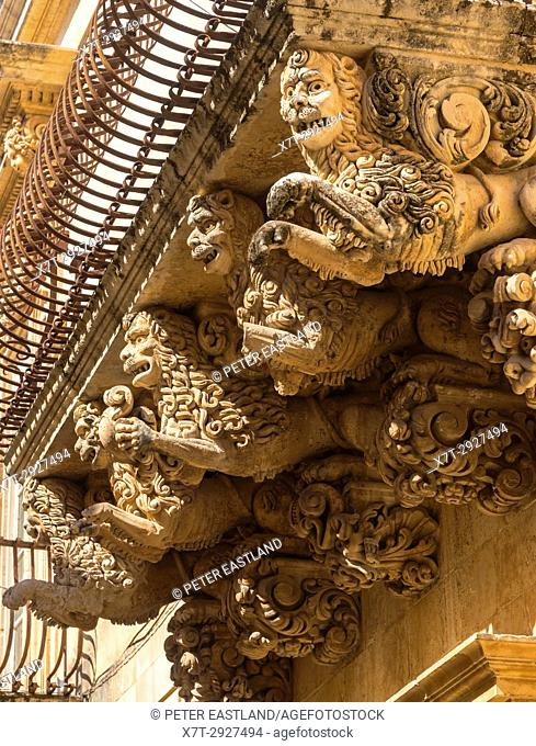 Ornately carved stone balcony supports on the Baroque Palazzo Villadorata in Noto, South Eastern Sicily,