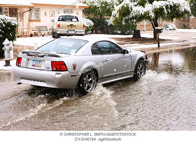 Vehicle braving the rising waters from thawing snow after a rare winter storm in Tucson Arizona