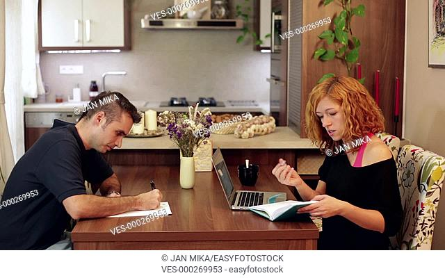 Couple of students writing homework in dining room at home