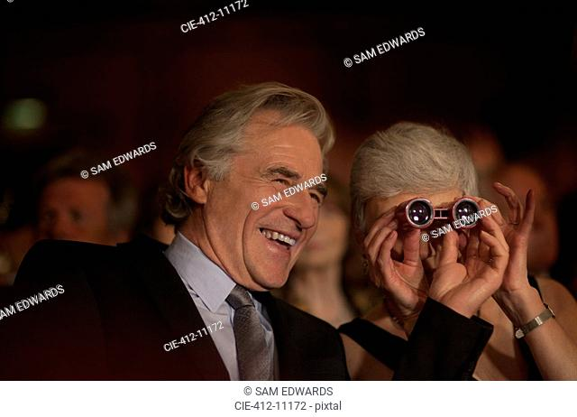Close up of smiling couple using opera glasses in theater audience