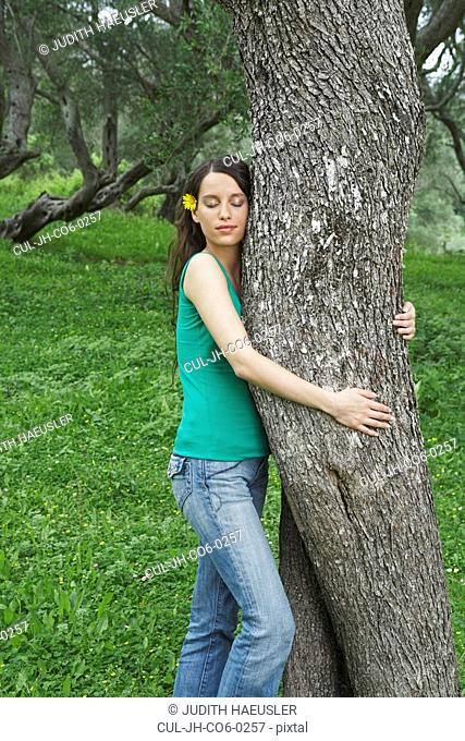 Young woman hugging tree in orchard with eyes closed