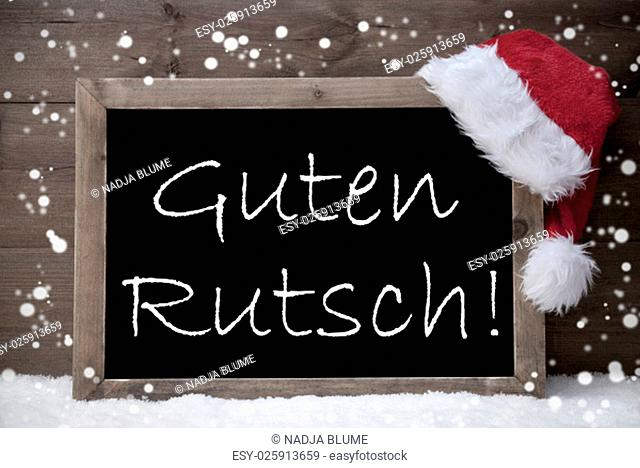 Gray Blackboard With Red Santa Hat On White Snow, Snowflakes. German Text Guten Rutsch Mean Happy New Year. Snowy Christmas Decoration With Brown Vintage Wooden...