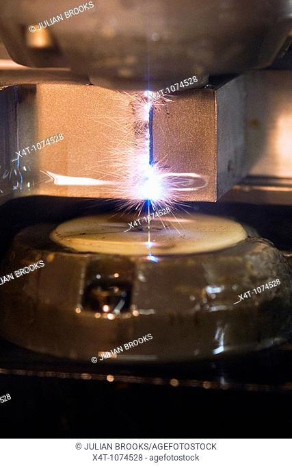 close up of a wire erosion machine shaping a piece of steel, precision engineering  Water cooling system turned off  Sparks created clearly visible