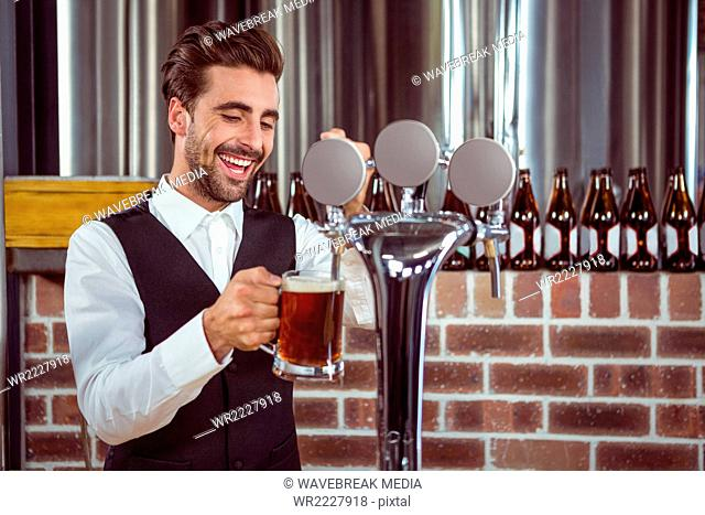 Handsome barman pouring a pint of beer