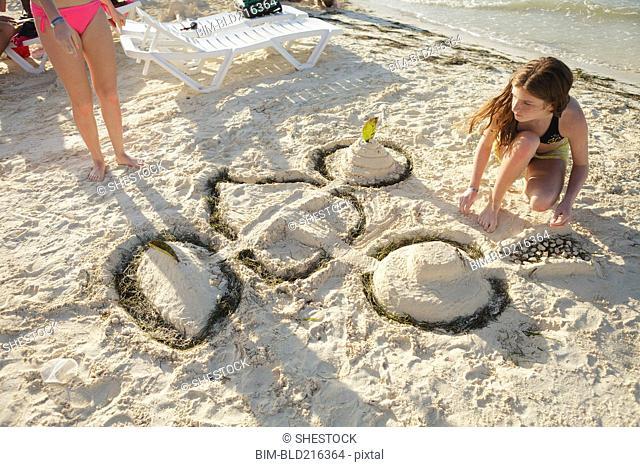 Caucasian teenage girl building sandcastle on beach