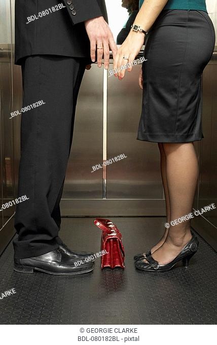detail of business couple standing together in elevator tenderly touching hands