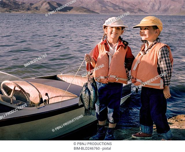 Portrait of Caucasian brother and sister posing with fish near boat