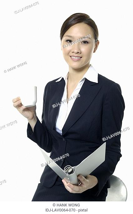Businesswoman holding a file and drinking tea