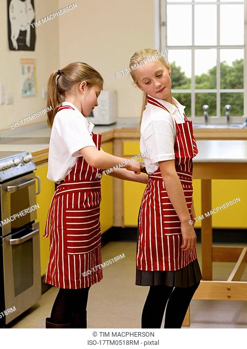 A girl helping to put on an apron