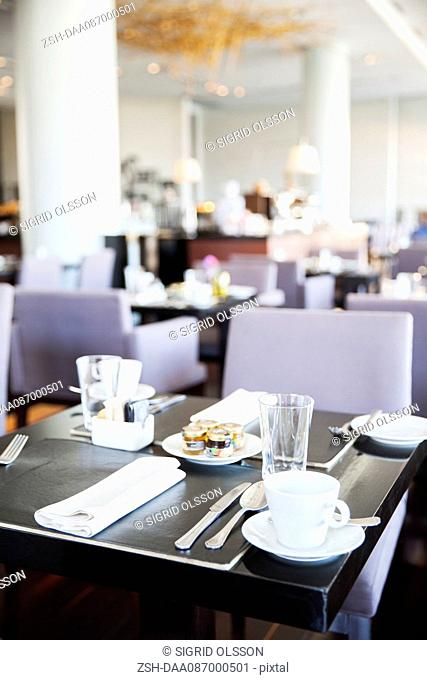 Place settings for breakfast in modern dining room