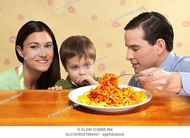 Close-up of a family sharing a platter of fettuccine pasta