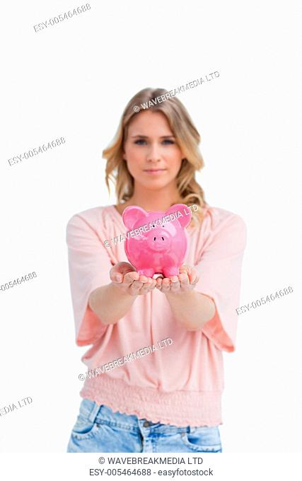 Woman holding a piggy bank in the palms of her hands