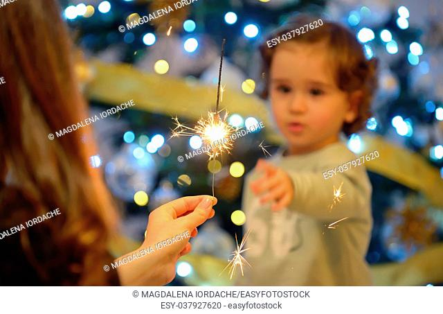 Teen girl holding sparklers and children