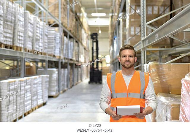 Portrait of confident man in factory hall wearing safety vest holding clipboard