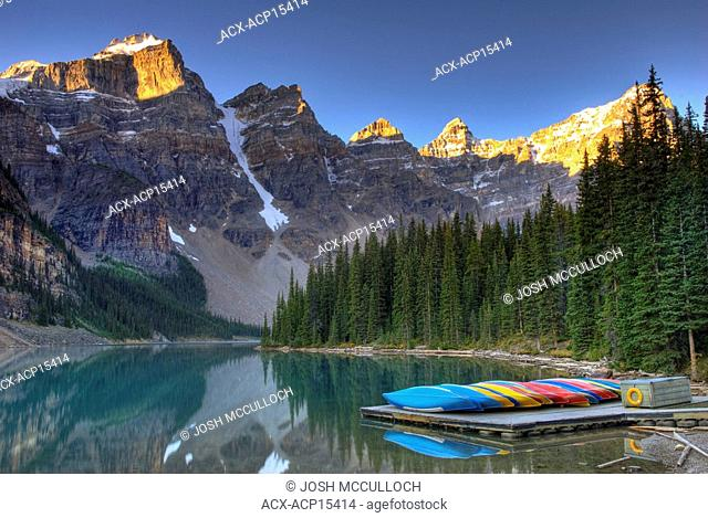 Frosty canoes sit on the dock at sunrise at Moraine Lake in the Valley of the Ten Peaks. Banff National Park, Alberta, Canada