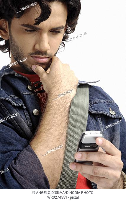 Teenage boy looking at sms message on mobile touching his right hand to chin and thinking MR 687T