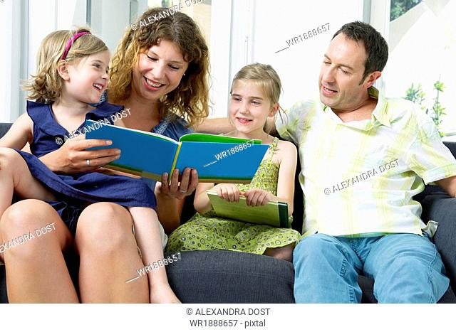 Family Reading Book In Living Room