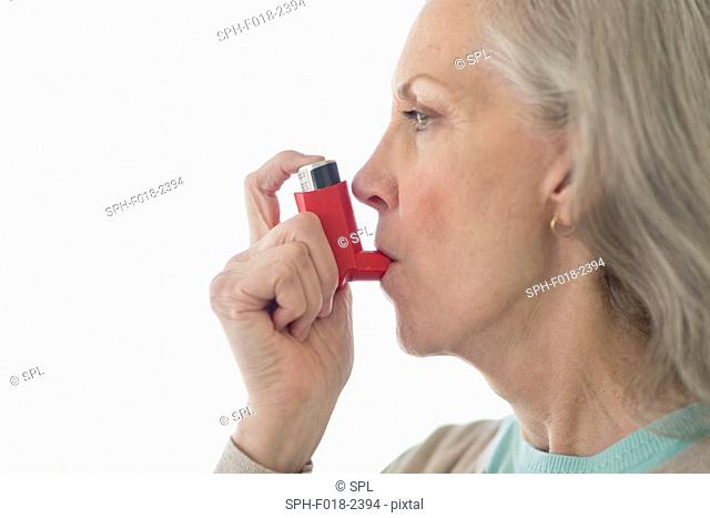 Senior woman using inhaler