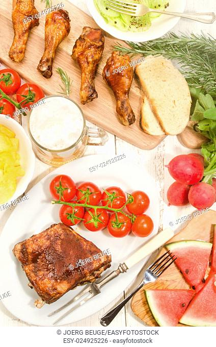 barbecue party with marinated ribs and chicken drumsticks, cucumber salad with crushed pepper, fresh tomato, chips, radish, watermelon and a glass of beer