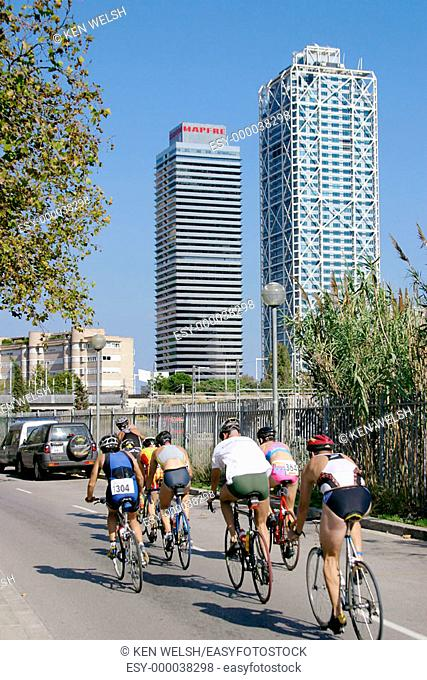 Athletes in bicycle event. Torre Mapfre and Hotel Arts. Barcelona. Catalonia. Spain
