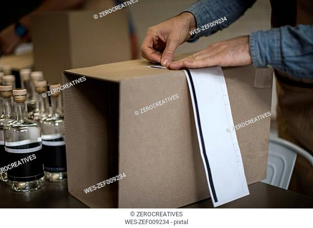Man adding note tape to box