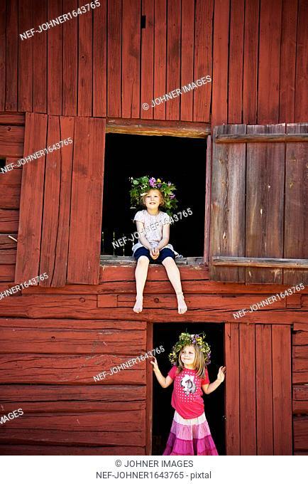 Girl wearing wreath of flowers sitting in barn window