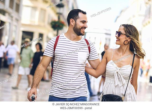 Spain, Andalusia, Malaga, happy tourist couple walking in the city