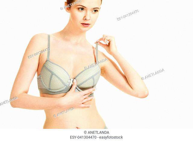 Femininity, brafitting, underclothes concept. Attractive slim red head woman in romantic grey bra underwear. Studio shot on white background