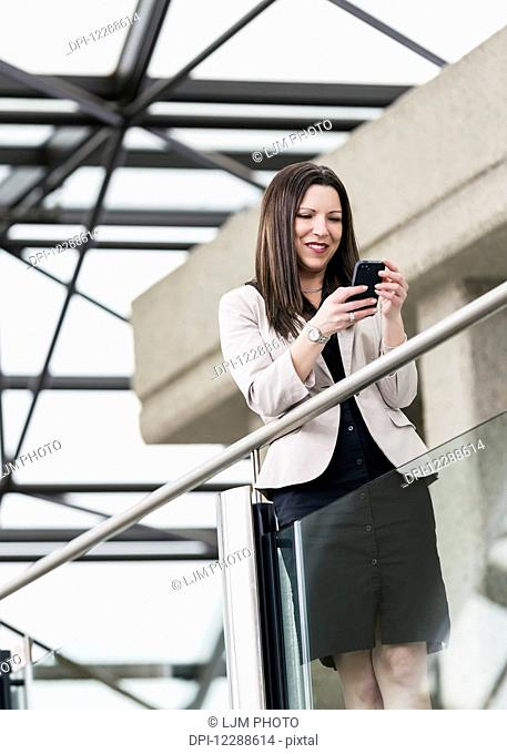 Mature business woman taking a break and texting on her smart phone; Edmonton, Alberta, Canada