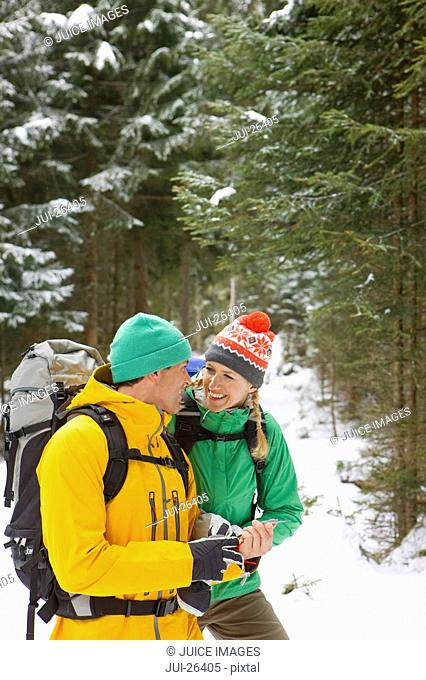 Happy couple with backpacks holding compass in snowy woods