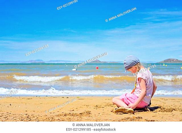 Little girl sitting and playing on the sandy beach
