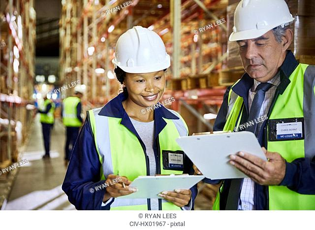 Manager and worker with clipboards meeting in distribution warehouse