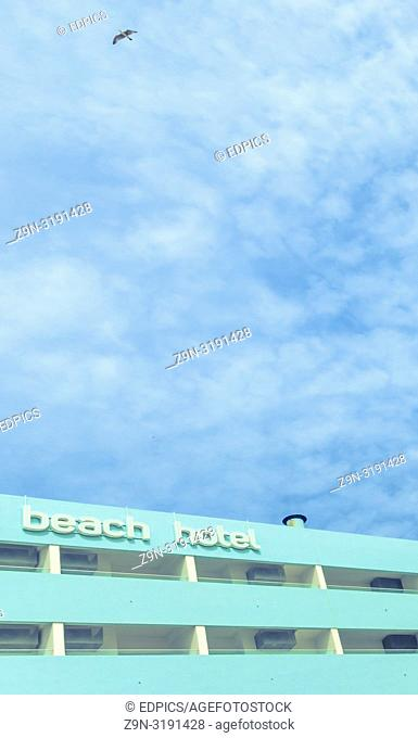 turquoise colored facade of hotel against sky, quarteira, algarve, portugal