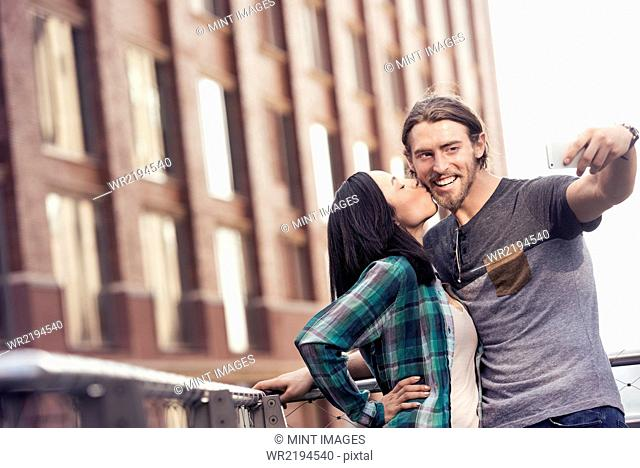 A woman kissing a man on the cheek, posing for a selfie by a large city building
