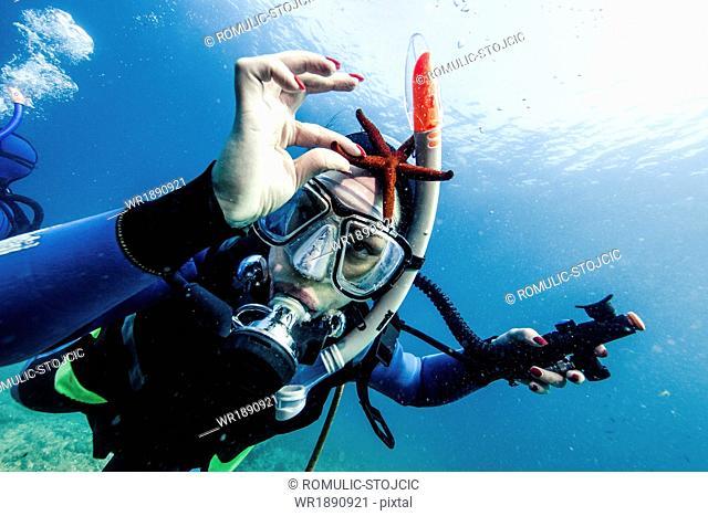 Diver Holding Sea Star, Adriatic Sea, Dalmatia, Croatia