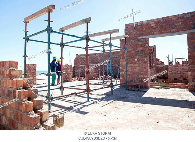 Builders talking on building site