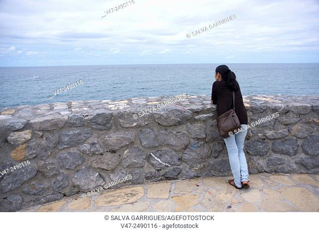 Woman looking out to sea at the Lighthouse Zumaia, Guipuzcoa, Basque Country, Spain, Europe