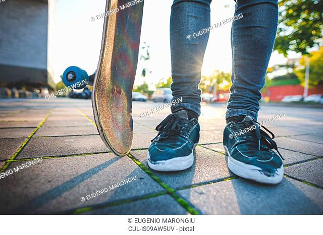 Legs and feet of young male urban skateboarder standing on sidewalk