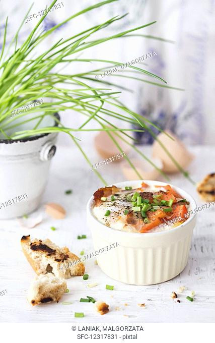 Baked eggs with bacon, tomatoes and chives
