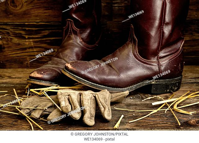 A concept image of worn cowboy boots and gloves