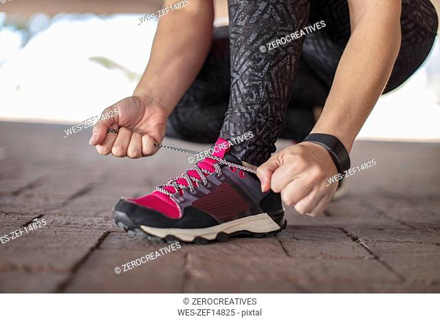 Sportive woman tying her shoes