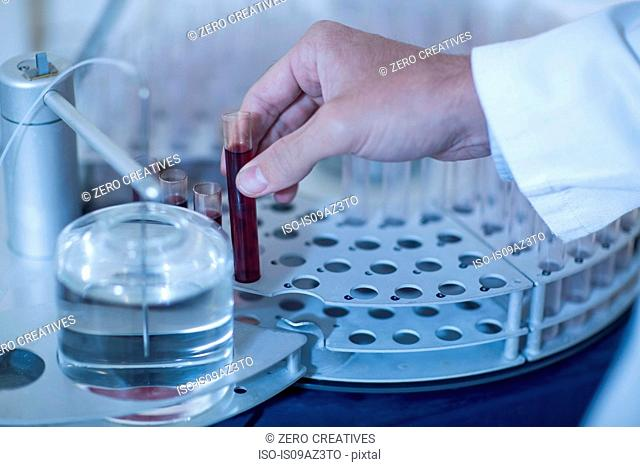 Man in laboratory, holding tube of liquid, close-up
