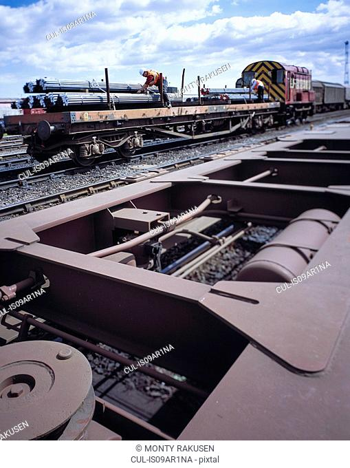 Workers loading freight train with steel in port, Grimsby, England, United Kingdom