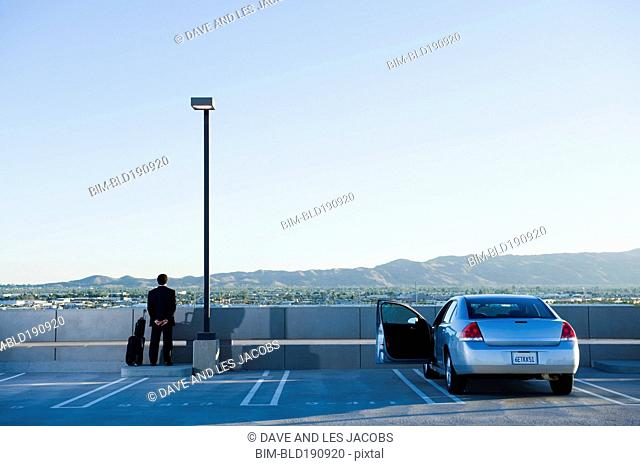 African businessman standing in parking lot at airport